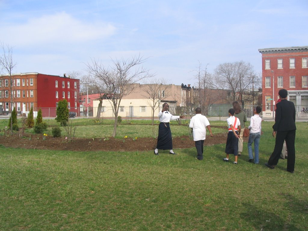 "Fig. 6 – Franklin Square Elementary School, Baltimore, MD, Fall 2006. Photograph by Christopher G. Boone. In this image, school teachers and students lead a tour of their recently ""greened"" playground. The original ""reading circle"" is visible in the background."