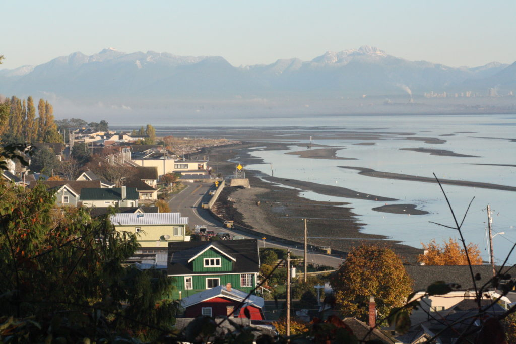 Maple Beach in Point Roberts with the Vancouver region in the background beyond the concrete marker.